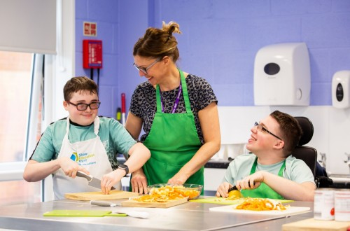 Two students and a teacher practising cooking skills