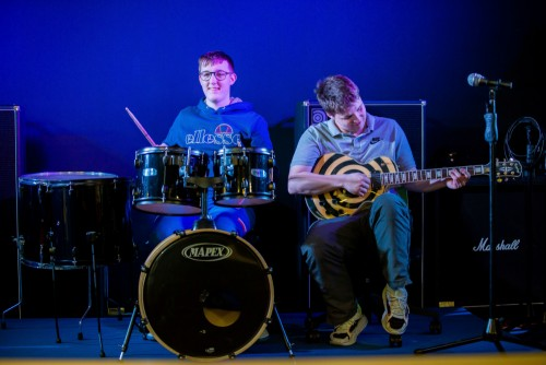 One student plays the drums and another plays the guitar in a performance
