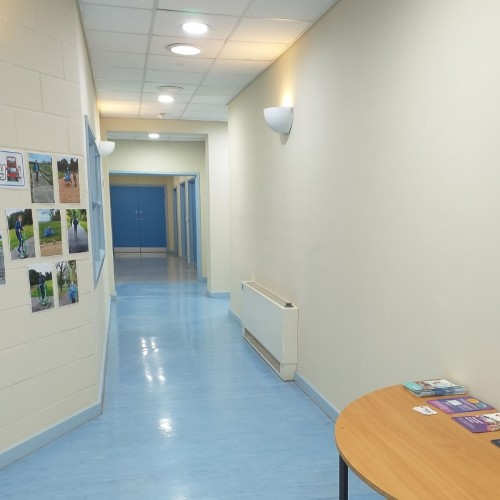 A corridor showing the wide open spaces inside the building, well lit and decorated in calming colours