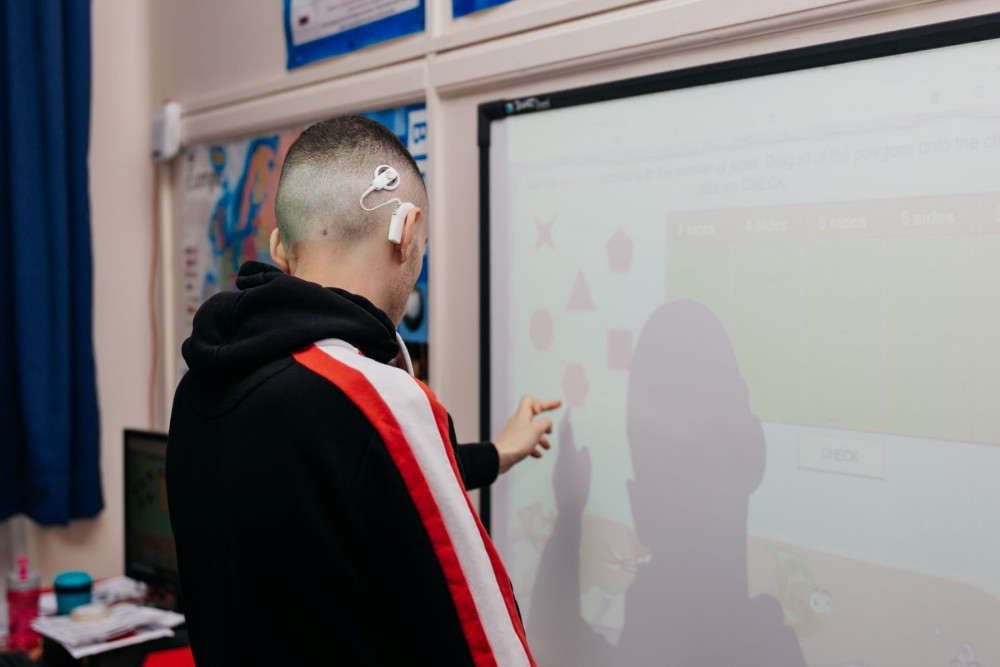 Student using the interactive board in an English session