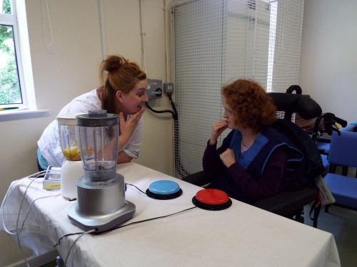A student being supported with Makaton to use a swich to operate a blender independently