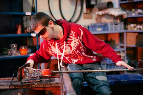 A student blowing glass, developing motor skills and concentration