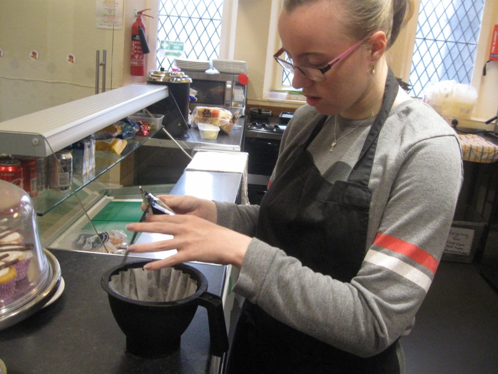 This image shows a learner on a work experience placement in a local church cafe, assisting with the coffee machine.