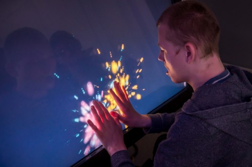 A student using a touch screen to create colourful interactive patterns