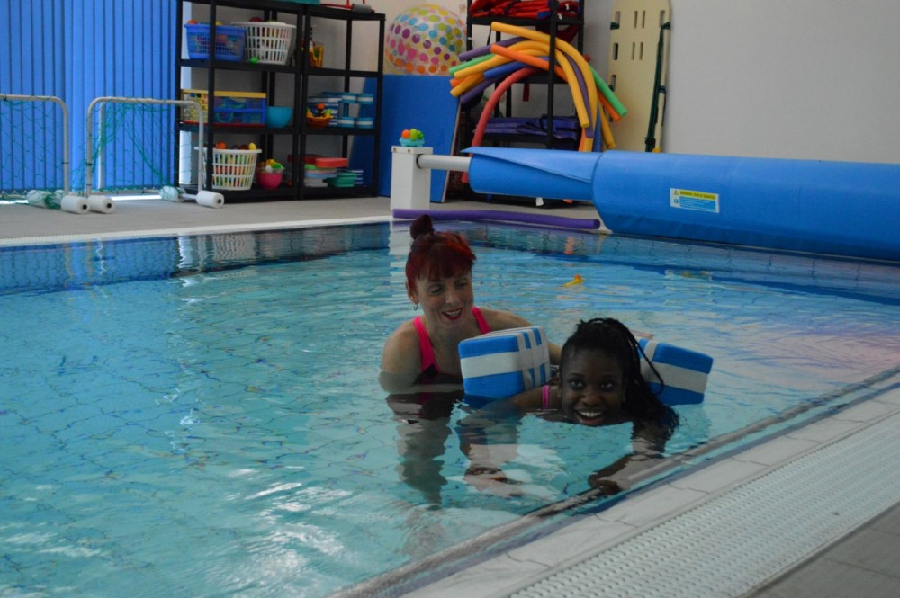 A student swimming in the state of art hydro pool with the assistance of a support worker