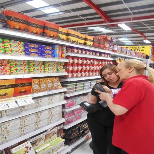 The learner is working in a supermarket as part of their supported internship placement and with staff support is checking stock levels.