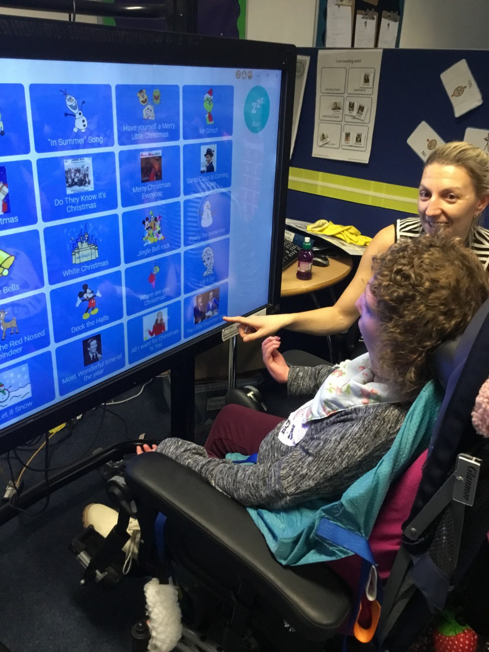 a learner selects a song from many choices on a large screen