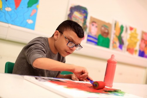A HBVC learner enjoying creative time working on a painting with a sponge roller, in the background are previous artworks by other learners.