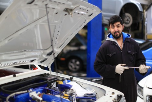 A HBVC learner in blue mechanics overalls on his work placement at a local car maintenance workshop.