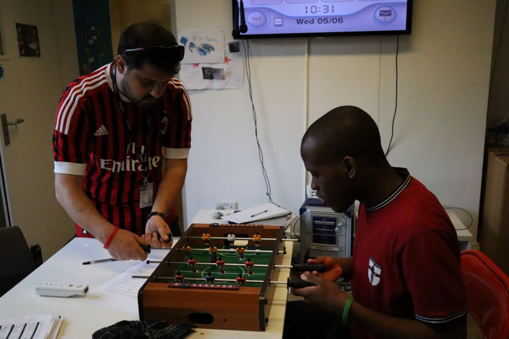 Student playing table football with Tutor