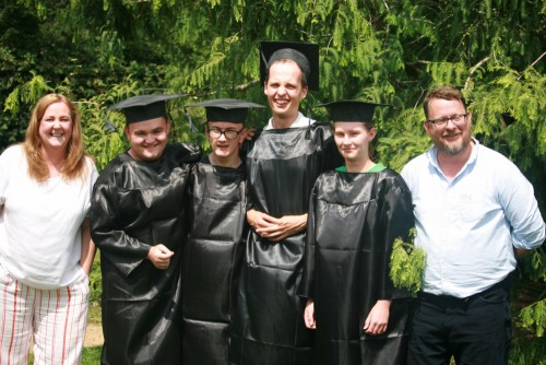Students at their graduation ceremony with members of staff